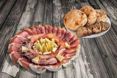 开胃菜美味盘用在老被风化的破裂的庭院表上设置的三个被发酵的皮塔小面包干大面包和长方形宝石切片 免版税库存图片