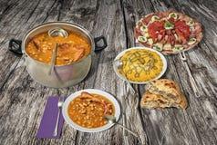 开胃菜美味盘用奥利维尔沙拉和被烘烤的豆供食与在老破裂的土气木庭院表上的小面包干 免版税库存图片