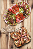 开胃菜美味盘用烤肉末大面包Cevapcici和在土气被打结的松木表上服务的鸡大腿 库存照片