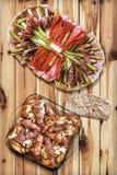 开胃菜美味盘用烤肉末大面包Cevapcici和在土气被打结的松木表上服务的鸡大腿 免版税库存照片