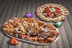 开胃菜美味盘Meze和唾液烤猪肉肉切片用在土气木庭院表上设置的复活节彩蛋 库存图片