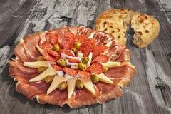 开胃菜美味盘Meze和在老被风化的破裂的片状木庭院表上的被发酵的皮塔小面包干被撕毁的大面包集合 免版税库存照片