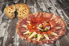 开胃菜美味盘Meze和在老被风化的破裂的片状木庭院表上的被发酵的皮塔小面包干被撕毁的大面包集合 库存照片