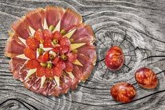 开胃菜美味食家盘用在老被打结的被风化的破裂的松林野餐桌上设置的五颜六色的复活节彩蛋 库存照片