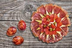 开胃菜美味食家盘Meze用在老被打结的被风化的破裂的松林野餐桌上设置的五颜六色的复活节彩蛋 免版税库存图片