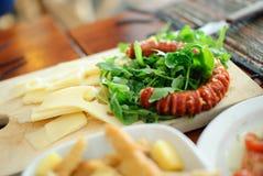 开胃菜,与芝麻菜和辣香肠 免版税图库摄影