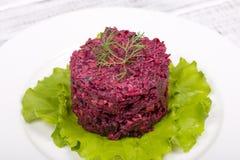 开胃菜,健康吃,可口红色甜菜沙拉用干李子,核桃,在白色板材的绿色莴苣在木桌里 Dieti 库存图片