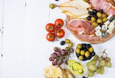 开胃菜,意大利开胃小菜,火腿,橄榄,乳酪,面包,葡萄,在白色木背景的梨 免版税库存图片