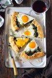 开胃菜:自创菠菜饼galette用鸡蛋和杯红葡萄酒 库存照片