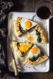 开胃菜:自创菠菜饼galette用鸡蛋和杯红葡萄酒 免版税库存照片