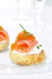 开胃菜-与盐味的三文鱼、红色鱼子酱和香葱的土豆小圆面包 免版税图库摄影