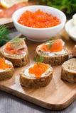 开胃菜-与盐味的三文鱼和红色鱼子酱的多士,垂直 免版税库存照片