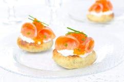 开胃菜-与盐味的三文鱼,红色鱼子酱的土豆小圆面包 免版税库存照片