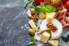 开胃菜-乳酪火腿面包蕃茄蓬蒿坚果酒 免版税库存照片