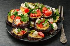 开胃菜-烤茄子用大蒜、希腊白软干酪和蕃茄 库存照片