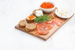 开胃菜-盐味的三文鱼、红色鱼子酱、多士和乳脂干酪 免版税库存图片