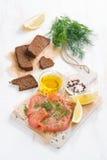 开胃菜-盐味的三文鱼、面包和成份在委员会 图库摄影