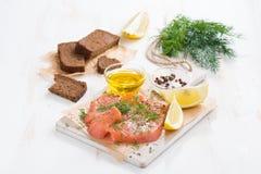 开胃菜-盐味的三文鱼、面包和成份在木板 免版税图库摄影