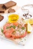 开胃菜-盐味的三文鱼和面包在一个木板,垂直 免版税库存照片