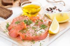 开胃菜-盐味的三文鱼和面包在一个木板 库存照片
