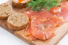 开胃菜-盐味的三文鱼,红色鱼子酱,在木板的多士 免版税库存照片