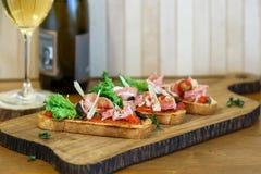 开胃菜-蕃茄、肉和乳酪在木板有瓶的酒 图库摄影