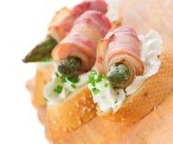 开胃菜-面包切片用烟肉、芦笋和软干酪 免版税库存图片