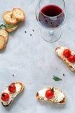 开胃菜bruschetta用乳酪和蕃茄和杯酒 图库摄影