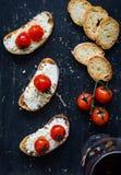 开胃菜bruschetta用乳酪和蕃茄和杯酒 免版税库存图片