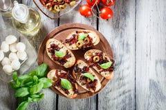 开胃菜bruschetta用各式各样的蕃茄、橄榄和mozarel 库存图片
