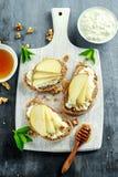 开胃菜bruschetta用梨、蜂蜜、核桃和酸奶干酪在白板 免版税库存照片