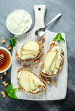开胃菜bruschetta用梨、蜂蜜、核桃和酸奶干酪在白板 库存照片