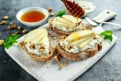 开胃菜bruschetta用梨、蜂蜜、核桃和酸奶干酪在白板 免版税库存图片