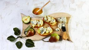 开胃菜bruschetta用梨、蜂蜜、核桃和酸奶干酪在轻的木委员会,轻的白色背景的 库存照片
