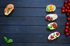 开胃菜bruschettas用蕃茄,三文鱼,乳脂状的乳酪, basi 免版税库存照片
