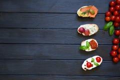 开胃菜bruschettas用蕃茄,三文鱼,乳脂状的乳酪, basi 免版税库存图片