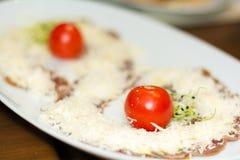 开胃菜carpaccio用帕尔马干酪、西红柿和新芽 图库摄影
