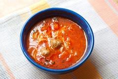 开胃蕃茄汤用细面条和丸子,在一张镶边桌布的蓝色板材,顶视图 lassic西班牙盘 免版税库存照片