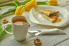 开胃薄煎饼用果子阻塞,一杯茶用柠檬,黄色郁金香、叉子和刀子 库存照片