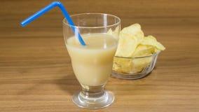 开胃酒、果汁和芯片在一块玻璃在木桌上 库存图片