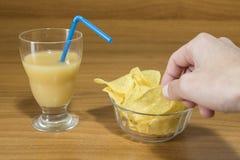开胃酒、果汁和芯片在一块玻璃在木桌上 图库摄影