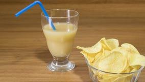 开胃酒、汁液和芯片在一块玻璃在桌上 库存照片