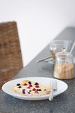 开胃酸奶干酪砂锅用在一块白色板材的野生莓果在一张灰色桌上 免版税库存照片