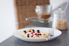 开胃酸奶干酪砂锅用在一块白色板材的野生莓果在一张灰色桌上 图库摄影