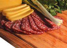 开胃香肠、乳酪、绿色和葱的构成在一个木板,孤立 图库摄影