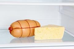 开胃香肠和乳酪在冰箱架子 免版税库存图片