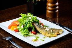 开胃鲜美被烘烤的鱼服务用蕃茄、桔子和sp 图库摄影