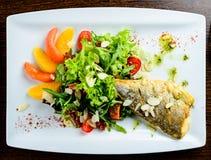 开胃鲜美被烘烤的鱼服务用蕃茄、桔子和sp 免版税库存图片