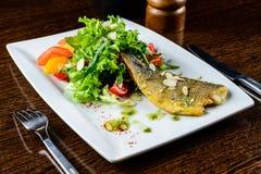 开胃鲜美被烘烤的鱼服务用蕃茄、桔子和sp 库存照片