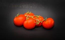 开胃水多的在深灰的藤红色蕃茄特写镜头视图  免版税图库摄影